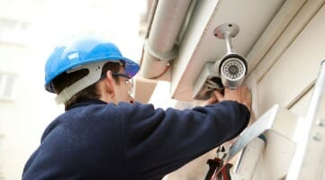 security camera installer on building